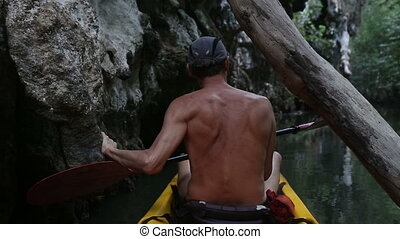 elder tanned man floating on kayak along the river near the...