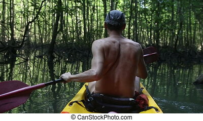 elder tanned man floating on kayak along the lagoon turns...