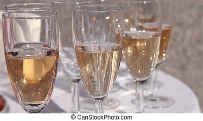 Glasses of champagne on white table close up