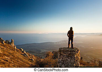 man on the cliff in mountains at sunset - thinking man on...