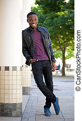 Cool guy smiling outdoors in black leather jacket