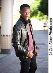 Black male fashion model posing in leather jacket - Portrait...