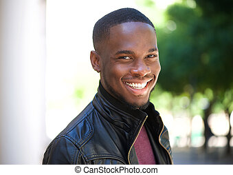 Cheerful young african american man smiling outside - Close...