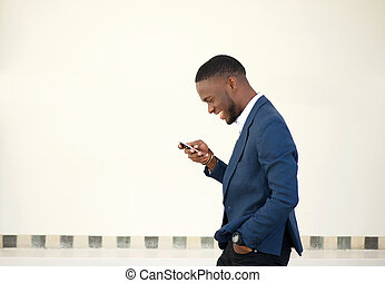 Smiling businessman walking and sending text message - Side...
