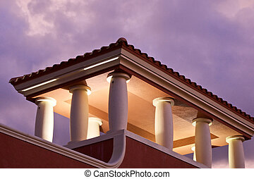 stormclouds with lit rooftop - behind a roof top portico...