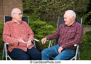 two men discussing - two senior men sitting in garden and...