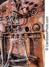 Old steam train engine with rust and damage