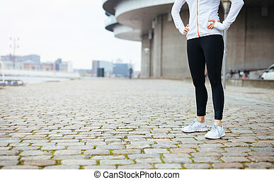 Fitness female standing on sidewalk in city - Cropped shot...