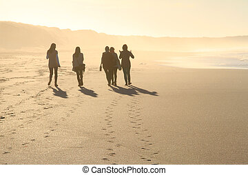 people walking in beach in sunset