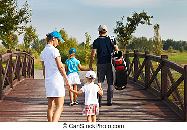 Family of golf players walking at the course - Family of...