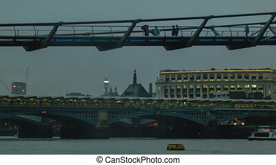 Millenium Bridge in cloudy weather, after sunset,...
