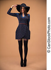 Full length portrait of a cute trendy woman over brown background