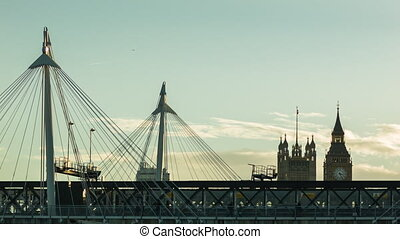 Hungerford Bridge at sunset, train passing by, Big Ben in...