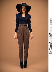 Full length portrait of a fashion woman standing over brown...
