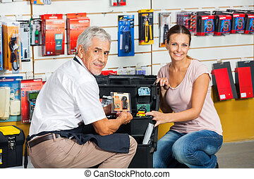 Salesman Showing Tool To Customer In Store - Portrait of...