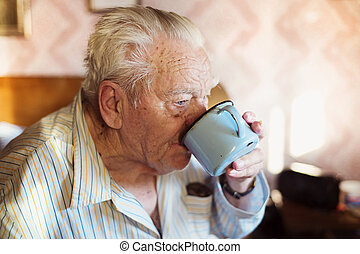 Senior man sitting on a bed and drinking water