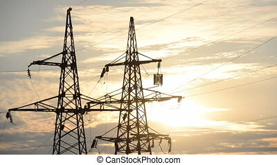 High-power lines, the setting sun, - High-power plants, the...