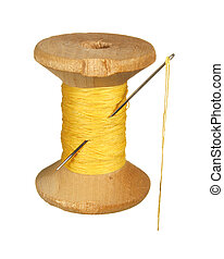 Old wooden spool of yellow thread and needle isolated on...