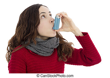 Asthma inhaler - Adult woman with asthma using inhaler to...
