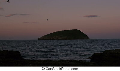 Night falling on Puffin Island, Anglesey, North Wales as...
