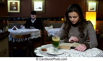 Boy and girl sitting in cafe. The girl reads an interesting book drinking tea, the boy drinks coffee