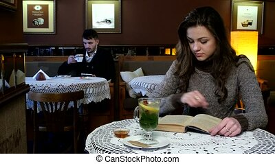 Boy and girl sitting in beautiful cafe. He`s reading something into his tablet computer, she reads a book while drinking mint tea with cinnamon