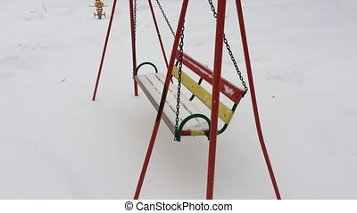 Empty swing metallic chains in winter time with snow.