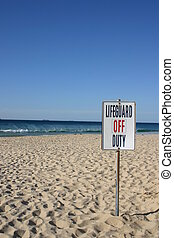 Summer beach scene with Lifeguard off Duty sign