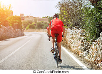 Male cyclist riding a bicycle on the road.