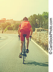 Male cyclist riding a bicycle on the road. Vintage effect.