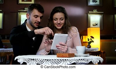 Young attractive couple sitting in a cafe and laughing watching something