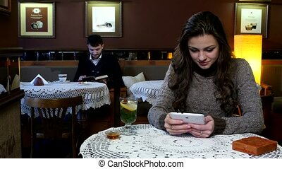 Laughing girl having tea in a coffee shop and boy reads an interesting book behind her