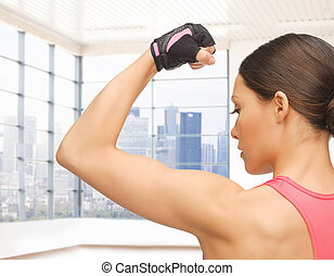 close up of sporty woman flexing her bicep - people,...