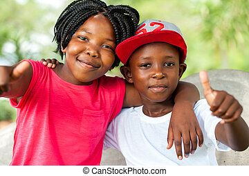 African brother and sister doing thumbs up. - Close up...