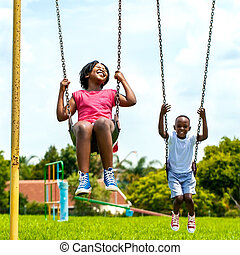 African kids having fun swinging in park. - Action portrait...
