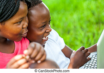 African kids having fun on laptop outdoors. - Close up face...