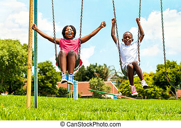 African kids playing on swing in neighborhood. - Action...