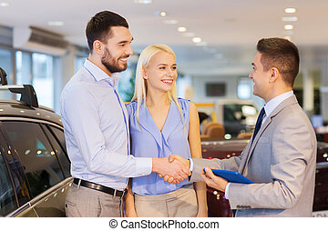 happy couple with car dealer in auto show or salon - auto...
