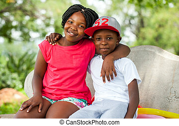 African kids sitting together on bench. - Close up portrait...