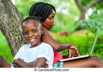 African kids under tree with laptop. - Close up portrait of...