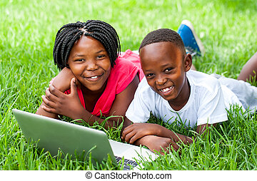 Two african kids laying on grass with laptop. - Close up...