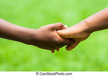 Detail of African kids holding hands - Extreme close up...
