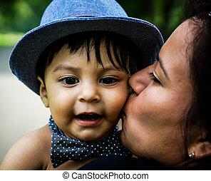 Smiling latino baby being kissed on cheek - Smiling latino...