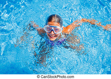 Girl in the pool - Cute happy young girl in goggles swimming...