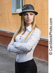 Beautiful blonde in a white blouse and a hat outdoors