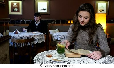 Beautiful girl with handsome guy in a cafe, she reads book and he uses tablet computer.