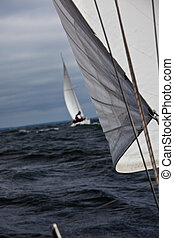 Sailing race - A sailboat trailing another in heavy weather.