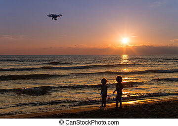 two children looking at a drone in flight on the beach