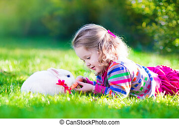 Little girl and real rabbit - Adorable curly toddler girl...