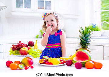 Little girl eating fruit - Cute curly little girl in a...